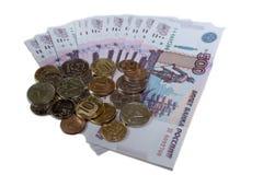 Las rublos acuñan contra el fondo de 500 rublos de billetes de banco isolared en el fondo blanco