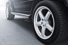 Las ruedas de coche se cierran para arriba en un fondo del asfalto imagen de archivo