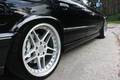 Las ruedas de coche se cierran para arriba en un fondo del asfalto Neumáticos de coche Primer de la rueda de coche foto de archivo