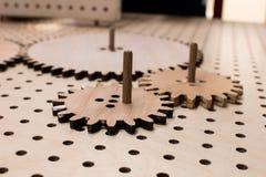 Las ruedas de engranaje de engranajes de madera en una tabla perforada montaron el toge imágenes de archivo libres de regalías