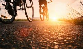 Las ruedas de la bici se cierran encima de imagen en el camino de la puesta del sol del asfalto Imágenes de archivo libres de regalías