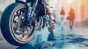 Las ruedas de la motocicleta allí son una parte posterior de la mujer en la ciudad Imagen de archivo libre de regalías