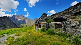 Las ruinas de la granja vieja en alpien las montañas Imágenes de archivo libres de regalías