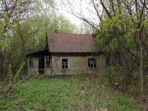 Las ruinas de una casa de madera abandonada en un pueblo del fantasma en el europeo al norte de Rusia imagen de archivo libre de regalías