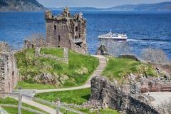 Las ruinas de Urquhart se escudan contra el barco en Loch Ness en Escocia fotografía de archivo