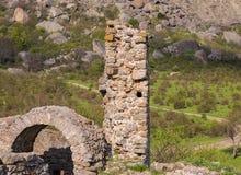 Las ruinas del castillo, elementos de los edificios arquean la piedra de la columna en el fondo de las altas montañas abajo crece Imagenes de archivo