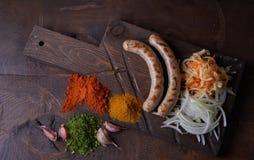 Las salchichas asaron a la parrilla el fondo de la comida, fondo de madera Foto de archivo libre de regalías