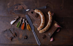 Las salchichas asaron a la parrilla el fondo de la comida, fondo de madera Imágenes de archivo libres de regalías