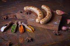 Las salchichas asaron a la parrilla el fondo de la comida, fondo de madera Imagenes de archivo