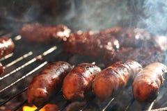 Las salchichas en barbacoa asan a la parilla con humo y la llama fotografía de archivo