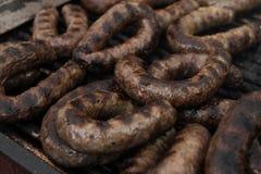 Las salchichas frescas asaron a la parrilla al aire libre en una parrilla del gas Barbacoa Fotografía de archivo