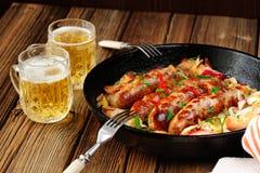 Las salchichas frieron en sartén del arrabio con dos tazas de cerveza Imagen de archivo libre de regalías