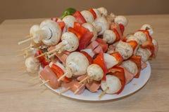 Las salchichas, los tomates, la pimienta y la hierba rellenaron y ensartaron setas foto de archivo