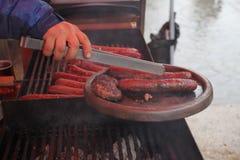 Las salchichas y las albóndigas frescas asaron a la parrilla al aire libre en una parrilla del gas Barbacoa Imagen de archivo libre de regalías
