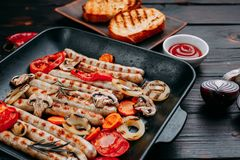 Las salchichas y las verduras asadas a la parrilla sirvieron en una cacerola de la parrilla con la salsa foto de archivo