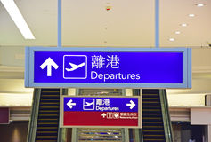 Las salidas firman adentro a Hong Kong International Airport con los caracteres chinos Fotografía de archivo libre de regalías