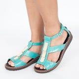 las sandalias de cuero azules con oro se aplicaron al pie de las mujeres en el fondo blanco Fotos de archivo