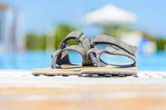 Las sandalias de cuero están al borde de la piscina Imágenes de archivo libres de regalías