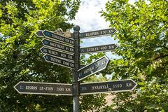 Las señales de dirección indican distancias a diversas ciudades Imagen de archivo
