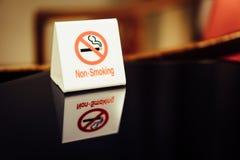 Las señales de peligro que prohíben humo en la tabla Fotografía de archivo libre de regalías