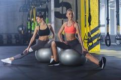 Las señoras deportivas están ejercitando con la bola de la aptitud dentro foto de archivo