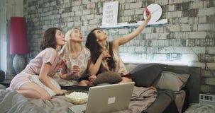 Las señoras jovenes étnicas multi que toman selfies en un dormitorio moderno, tienen un partido de pijamas que sostiene los vidri almacen de video