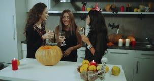 Las señoras jovenes de la noche de Halloween que pasan gran tiempo junto en casa van de fiesta el vino de consumición, sonriendo, metrajes