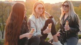 Las señoras jovenes del ocio moderno meriendan en el campo puesta del sol del parque almacen de video