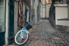 Las señoras montan en bicicleta con la cesta parqueada en la calle en viejo europeo Imagen de archivo libre de regalías