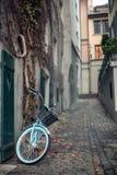 Las señoras montan en bicicleta con la cesta parqueada en la calle en viejo europeo Fotografía de archivo libre de regalías