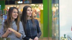 Las señoras que hacen una pausa la ventana de las compras en la alameda, discuten emocionalmente el hacer compras