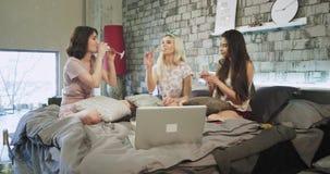 Las señoras sonrientes carismáticas tienen un partido casero, en un dormitorio moderno beben alegrías del champán y el abrazo almacen de video