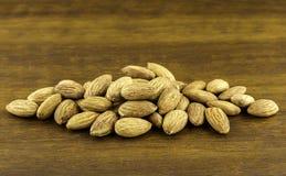 Las semillas de las almendras vierten de la cuchara de madera en el fondo de madera texturizado, visión superior Fotografía de archivo