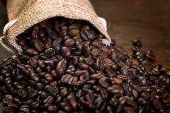 Las semillas del café con algunos bolsos del yute llenaron de los granos de café Imagen de archivo libre de regalías
