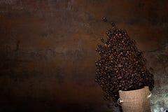 Las semillas del café con algunos bolsos del yute llenaron de los granos de café Imagenes de archivo