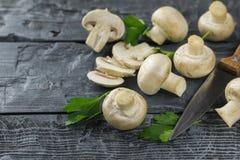 Las setas frescas con un cuchillo dispersaron en la tabla de madera oscura La comida vegetariana está en la tabla Fotografía de archivo libre de regalías