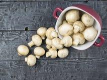 Las setas frescas se vierten de una taza púrpura en una tabla de madera La comida vegetariana está en la tabla Imagen de archivo
