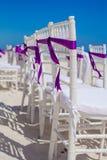 Las sillas blancas de la boda adornadas con púrpura arquean encendido Imagen de archivo libre de regalías