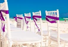 Las sillas blancas de la boda adornadas con púrpura arquean encendido Fotos de archivo libres de regalías