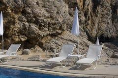 Las sillas de cubierta acercan a la piscina Fotografía de archivo
