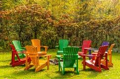 Las sillas de madera del adirondack arreglaron en un círculo alrededor de un hoyo del fuego imagen de archivo libre de regalías