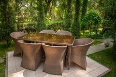 Las sillas de mimbre y la tabla est?n en el jard?n cerca de ?rboles imagen de archivo