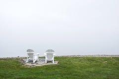 Las sillas de Muskoka en el lago afrontan con el cielo blanco Fotos de archivo