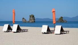 Las sillas de playa con los paraguas en la arena varan en la playa Foto de archivo libre de regalías