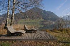 Las sillas de playa de madera en el lago apuntalan schliersee Foto de archivo libre de regalías