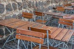 Las sillas de tablas vacías de la terraza del café mojaron la pared de madera de la primavera fotos de archivo