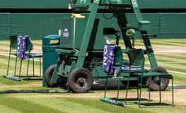 Las sillas del ` de los jugadores con la toalla plegaron la parte posterior, y un paraguas verde y púrpura en la hierba foto de archivo libre de regalías