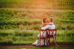 Las sillas que se sientan que se besan jovenes hermosas de novia y del novio en la puesta del sol se encienden Foto de archivo libre de regalías