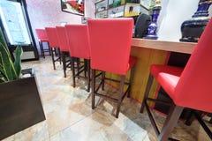Las sillas rojas altas colocan el contador cercano de la barra Fotos de archivo libres de regalías