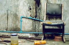 Las sillas viejas fueron dejadas en la pared vieja fotos de archivo